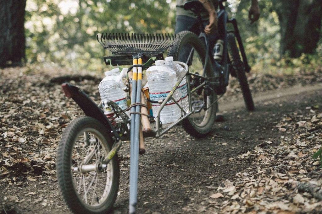 una bicicletta mountain bike ed un carrellino carico di acqua e di attrezzi per la manutenzione dei sentieri