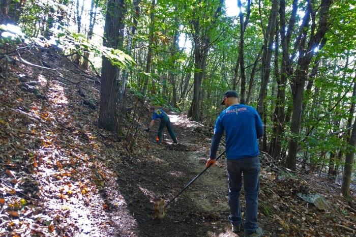 volontari al lavoro su un sentiero con i rastrelli